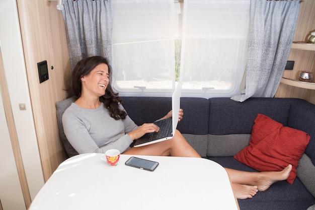 Mulher trabalhando em um trailer ou trailer como escritório