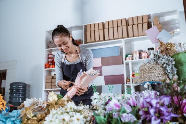 Mulher trabalhando em uma floricultura usando avental e preparando uma flor