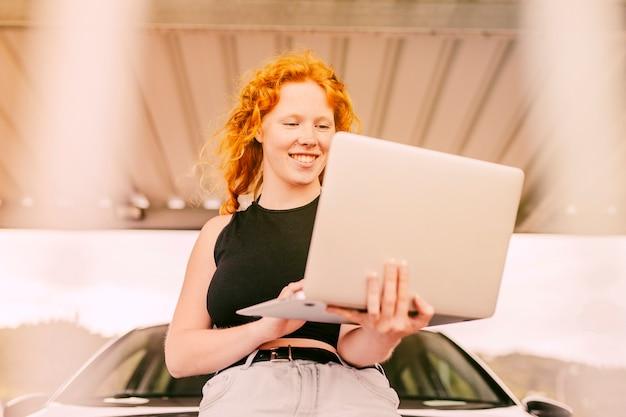 Mulher, trabalhando, laptop, ao lado, car, ao ar livre
