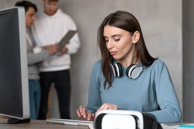 Mulher trabalhando na área de mídia com colegas do sexo masculino
