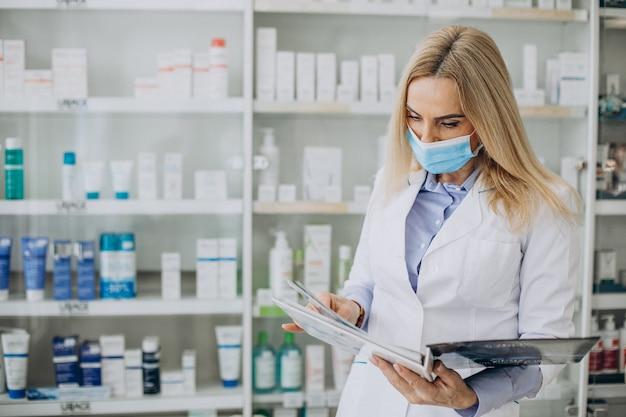 Mulher trabalhando na farmácia e vestindo casaco