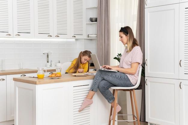 Mulher trabalhando na mesa com a garota em cena completa