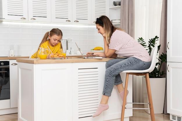 Mulher trabalhando na mesa com uma garota
