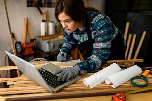 Mulher trabalhando na oficina e usando laptop