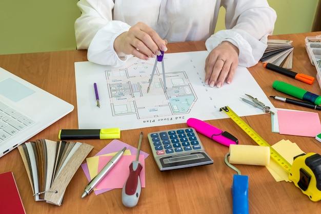 Mulher trabalhando na planta da casa do escritório e no laptop