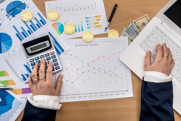 Mulher trabalhando no escritório - laptop gráfico de negócios bitcoin e dólar