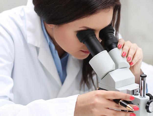 Mulher trabalhando no laboratório com um microscópio