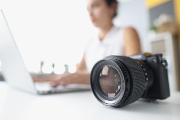 Mulher trabalhando no laptop ao lado do controle remoto da câmera trabalhando em ações para o conceito de fotos