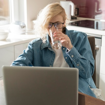 Mulher trabalhando no laptop e água potável