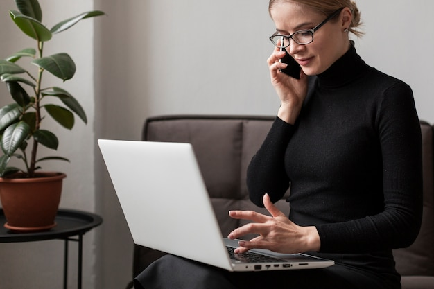 Mulher trabalhando no laptop e falando no telefone