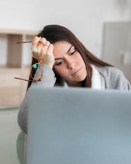 Mulher trabalhando no laptop e segurando óculos