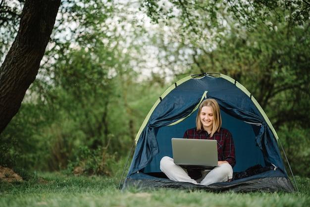 Mulher trabalhando no laptop em uma barraca na natureza. jovem freelancer sentado no acampamento. relaxando no local de acampamento na floresta, prado. trabalho remoto, atividade ao ar livre no verão. garota feliz relaxante, trabalho nas férias.