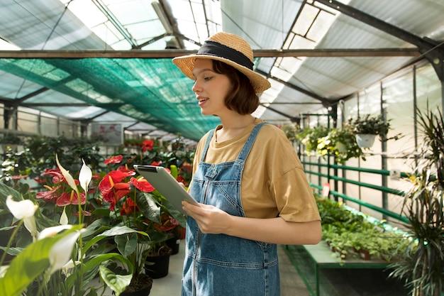 Mulher trabalhando sozinha em uma estufa sustentável