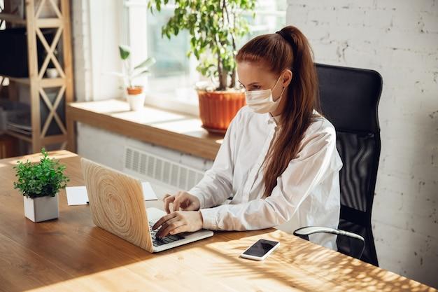 Mulher trabalhando sozinha no escritório durante o coronavírus ou quarentena cobiçada usando máscara facial