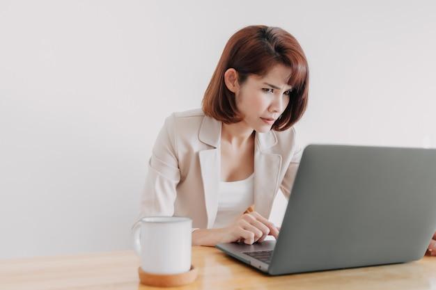 Mulher trabalhando usando laptop na mesa do escritório com fundo branco