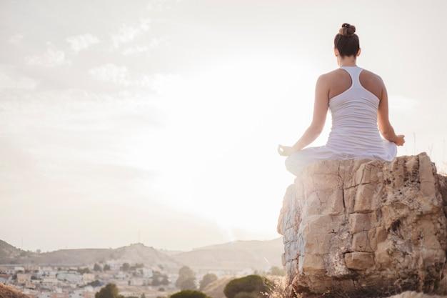Mulher tranquila meditando ao pôr do sol