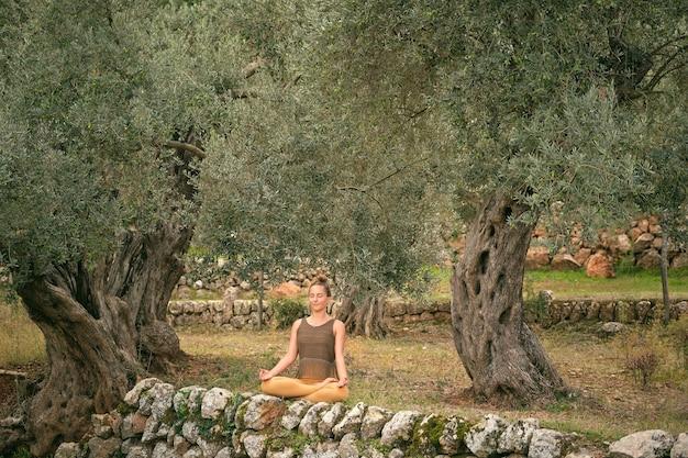 Mulher tranquila praticando ioga em pose de lótus no parque