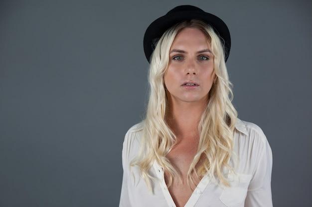 Mulher transgênero usando chapéu em pé sobre uma parede cinza