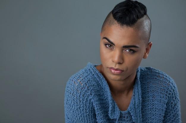 Mulher transgênero vestindo suéter azul sobre parede cinza