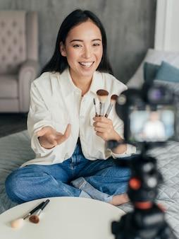 Mulher transmitindo ao vivo sobre ferramentas de maquiagem com a câmera