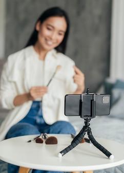 Mulher transmitindo ao vivo sobre ferramentas de maquiagem com o telefone