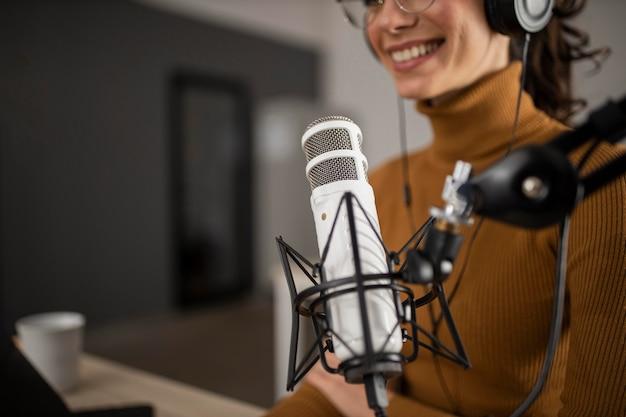 Mulher transmitindo no rádio enquanto sorri