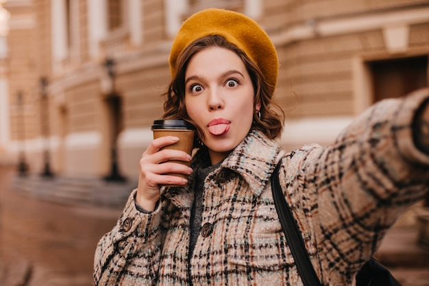 Mulher travessa com roupa de outono fazendo selfie contra a parede da cidade