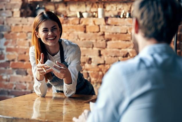 Mulher traz café para o serviço de trabalho do garçom do cliente
