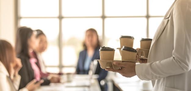 Mulher traz copos de papel para levar com café entram no escritório durante grupo de funcionários, colegas sentados e trabalham na mesa de trabalho e, em seguida, cumprimentam e felizes com gentileza. conceito de trabalho em equipe.
