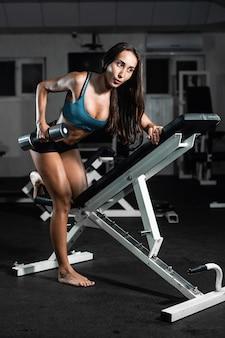 Mulher treina no ginásio. atlética mulher treina com halteres, bombeando seus bíceps