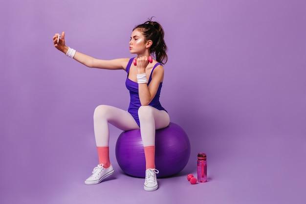 Mulher treinadora de fitness senta-se na bola, faz exercícios com halteres e faz selfie na parede roxa
