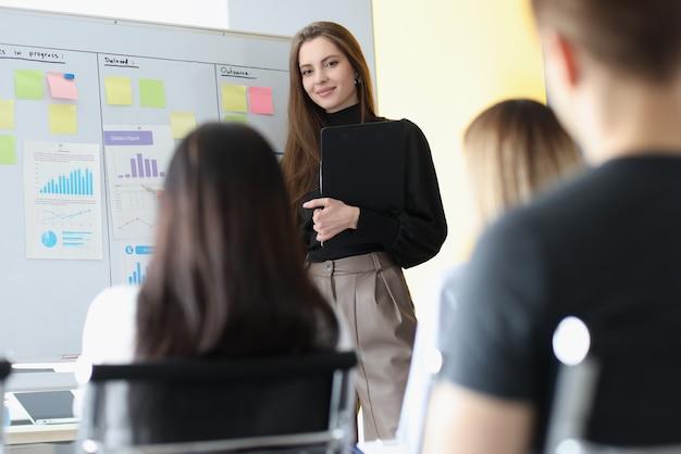 Mulher treinadora de negócios em frente ao quadro-negro na frente de alunos ouvintes