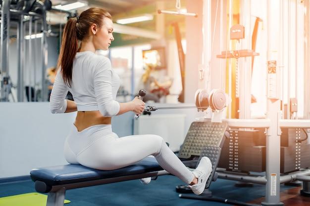 Mulher treinando com aparelho de musculação