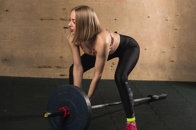 Mulher treinando com barra