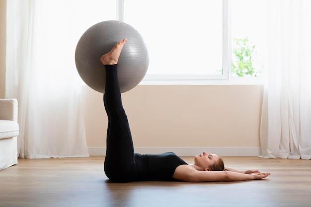 Mulher treinando com bola de ginástica tiro completo