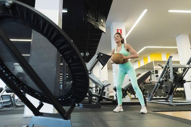 Mulher treinando com bola de medicina amarela.
