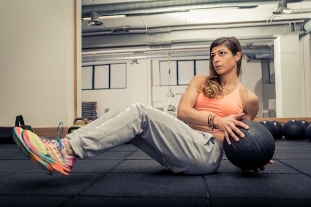 Mulher treinando com bola médica no ginásio