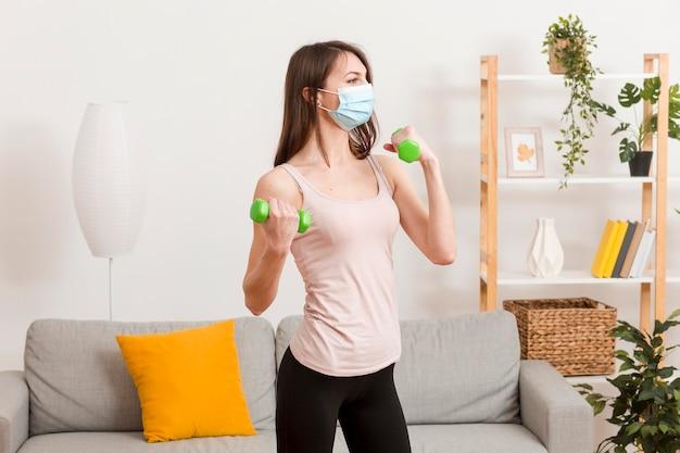 Mulher treinando com máscara