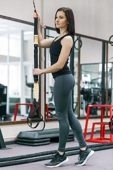 Mulher treinando com sistema de loop de fitness no ginásio