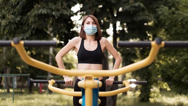 Mulher treinando com uma máscara médica