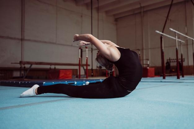 Mulher treinando de lado para as olimpíadas de ginástica