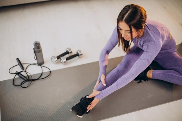 Mulher treinando em casa no tatame usando halteres e pular corda