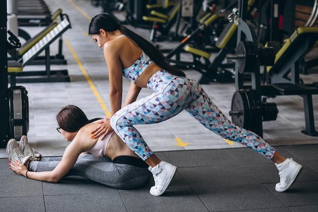 Mulher treinando na academia com instrutor de fitness feminino
