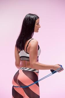 Mulher treinando no sportswear com corda de pular