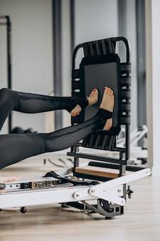 Mulher treinando pilates no reformador