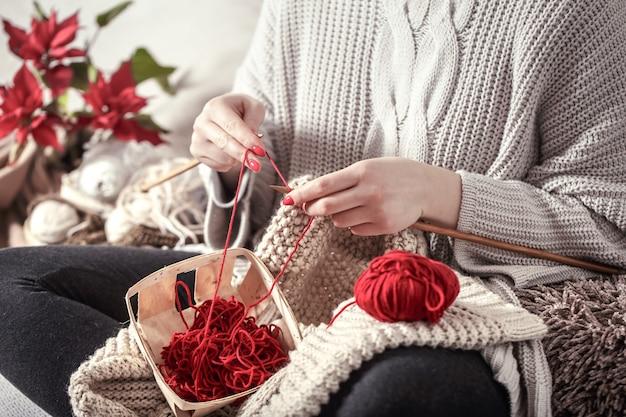 Mulher tricota agulhas de tricô no sofá