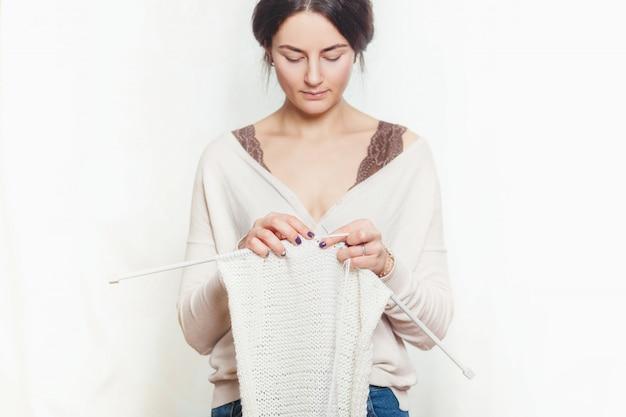 Mulher tricota roupas de lã