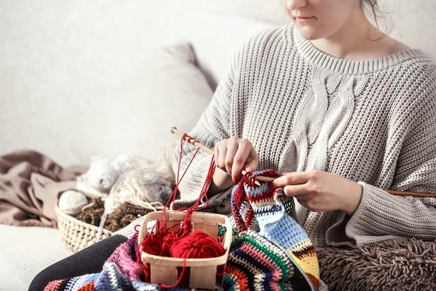 Mulher tricotando agulhas de tricô no sofá