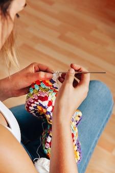 Mulher tricotando com agulha