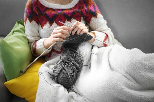 Mulher tricotando no sofá